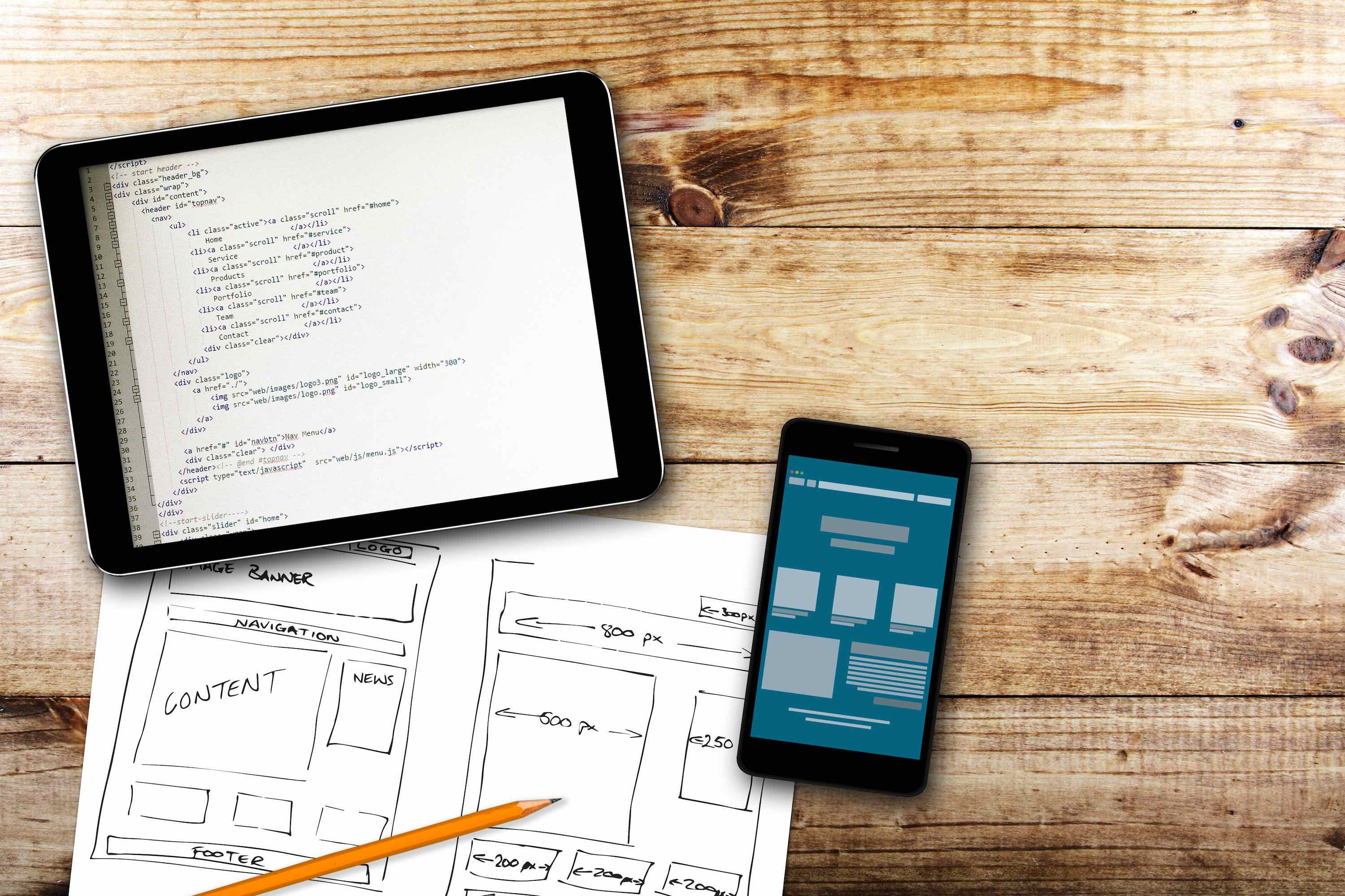 Software wireframe sketch and programming code on digital tablet
